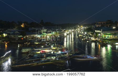 Soc Trang, Vietnam - January 21, 2017: Dawn on floating market with busy night boats lights twinkling transporting agricultural goods to trade in preparation for  Lunar New Year in Soc Trang, Vietnam