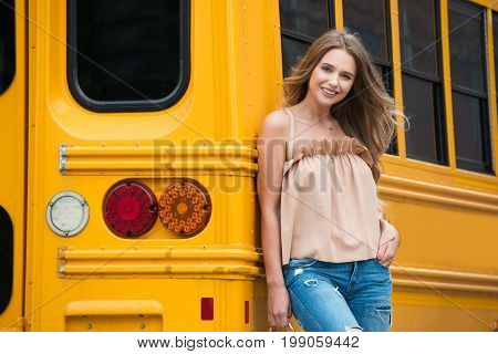Beautiful high school student standing near yellow school bus