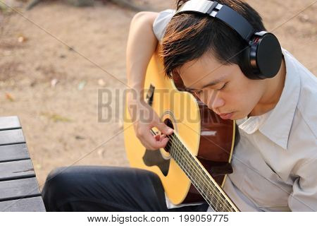 Selective focus of young relaxed man is playing acoustic guitar in outdoor.