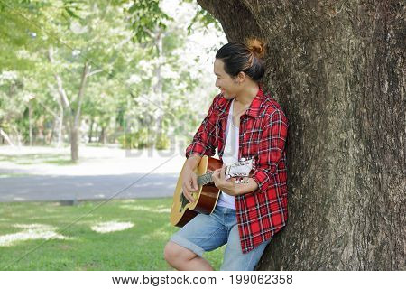 Young man is leaning to play acoustic guitar at the park outdoor.