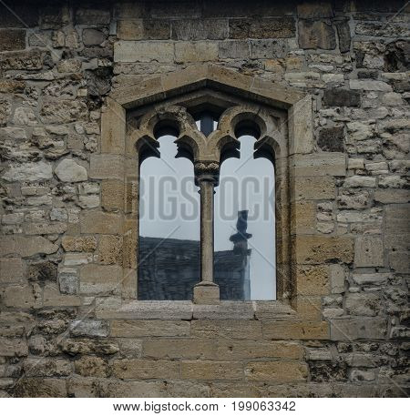 The Old And Ancient Window With Glass Reflection In Stone Wall