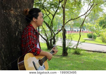 Portrait of guitarist or musician is playing acoustic guitar in the beautiful nature park background.