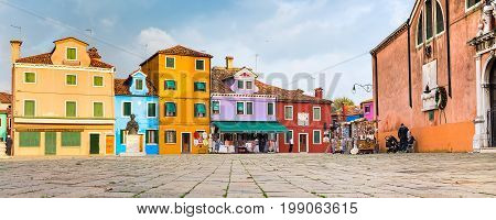 Burano Island, Venice, Italy - November 11, 2014: Venice landmark, Burano island, town square with colorful houses and people selling souvenirs