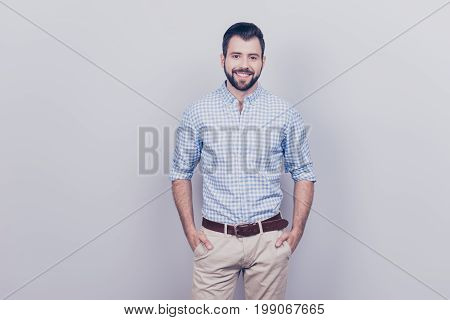 Success Concept. Stylish Young Smiling Bearded Brunet Is Standing On Pure Gray Background. He Looks