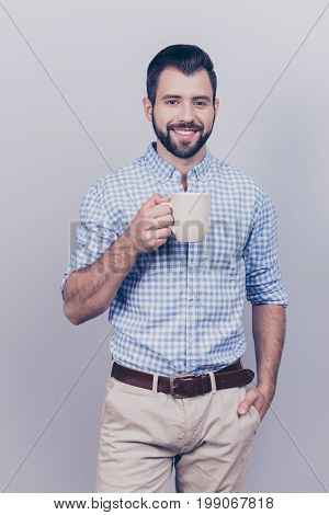 Young Dreaming Brunet Bearded Worker In Formal Wear Is Standing With The Mug Of Tea Isolated On Pure