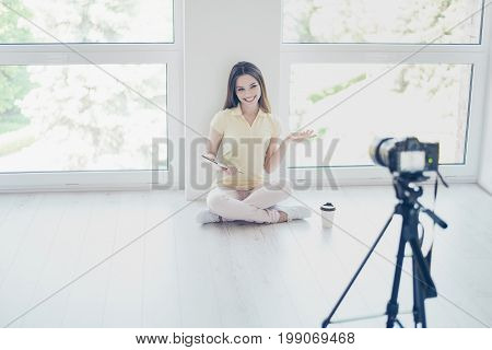 Video Camera Is Recording Pretty Brunette Girl Blogger, Talking With A Tablet In Hand, Sitting At Th