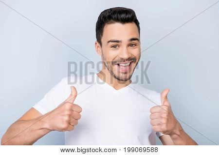 Smiling Young Stylish Bearded Brunet Student In  Casual White T Shirt Is Standing On Light Backgroun