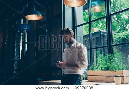 Young Well Dressed Entrepreneur Is Browsing On His Mobile Phone At The Modern Office, Behind Is A Wi