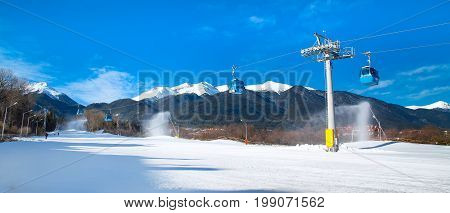 Bansko, Bulgaria - February 19, 2015: Ski resort panorama with pine trees, white snow peaks of the mountains, ski slope and snow canons