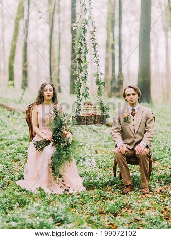 The newlyweds in the vintage clothes are sitting on the chairs near the hanging stump with the wedding green cake on it. The bride is holding the huge bouquet