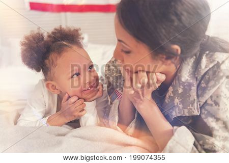 Fondly looks. The close up of adorable little girl and her mother in a military uniform looking at each other with fondness while resting their chins on hands