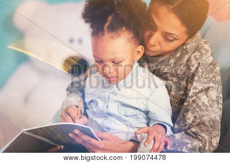 Curious child. Sweet curly girl sitting in her mothers embrace and paying close attention to things her military mother putting down in the notebook