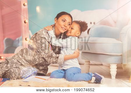 Love you mum. Sweet little daughter sitting on the floor and hugging her gorgeous mother wearing a US military uniform while both of them looking happy
