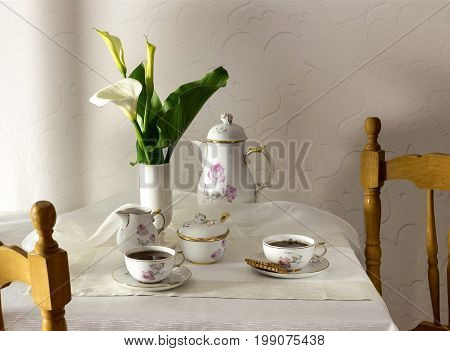 Tea set and a bouquet of calla lilies on a table closeup