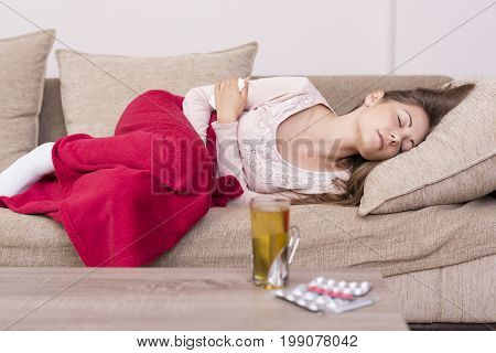 Young woman lying on a bed covered with blanket holding her stomach in pain