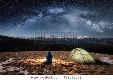 Female Tourist Have A Rest In Her Camp At Night. Woman Sitting Near Campfire And Green Tent Under Be