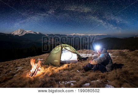 Male Tourist Have A Rest In His Camp At Night. Man With Lighting Headlamp Sitting Near Campfire And