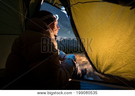 View From Inside A Tent On The Male Tourist Have A Rest In His Camping At Night. Man With A Headlamp
