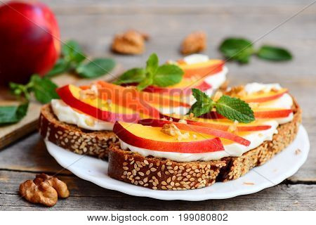 Easy sandwiches with cream cheese, fresh nectarines, walnuts and mint on a plate and on a vintage wooden table. Cream cheese sandwich recipe for kids. Rustic style. Closeup