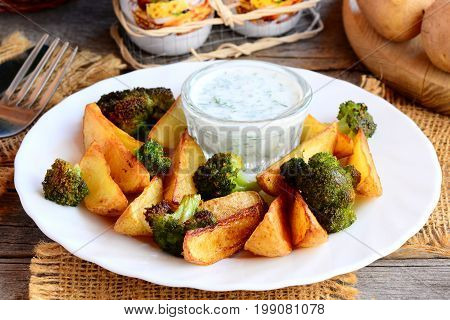 Oven roasted vegetables recipe. Roasted potatoes slices and broccoli with sauce on a white plate and an old wooden table. Rustic stile. Closeup
