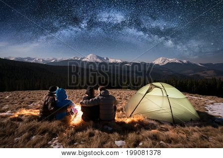 Silhouette Of Four People - Two Romantic Couples Are Sitting Together Beside Camp And Tent Under Bea