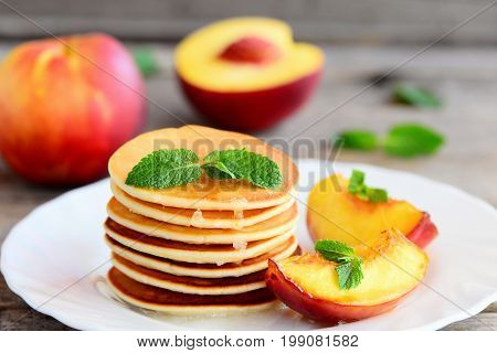 Homemade pancakes with sirup, nectarine and mint on a plate. Easy basic pancakes for breakfast. Closeup