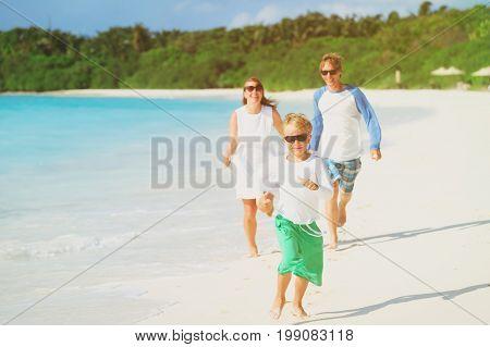 happy family with kid play run on tropical beach