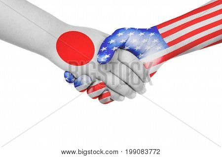 Handshake between Japan and United States of America with flags painted on child's hands in isolated white background