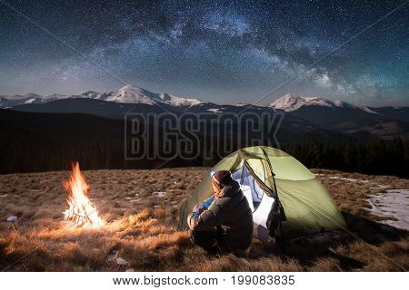 Male Tourist Have A Rest In His Camping In The Mountains At Night. Man With A Headlamp Sitting Near