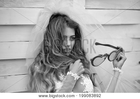 lady with long hair in wedding dress and bride veil holding glasses in heart shape on wooden background black and white