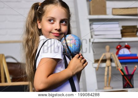 Schoolgirl With Happy And Flirty Face Holds Small Globe Model