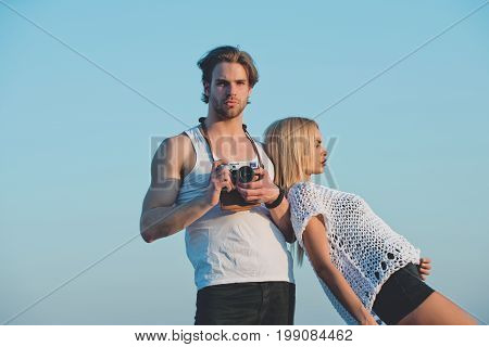 Beauty and art fashion. Man with muscular body with girlfriend. Girl with photographer outdoor. Couple in love and romance. Guy with photo camera on athletic chest.