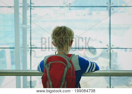 little boy looking at planes in the airport, travel concept