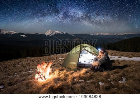 Male Tourist Enjoying In His Camp At Night. Man With A Headlamp Sitting Near Campfire And Tent Under