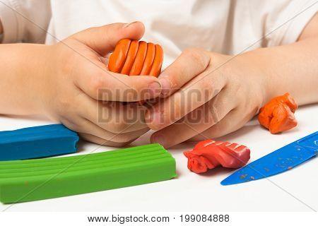 hands of child molding from orange plasticine closeup