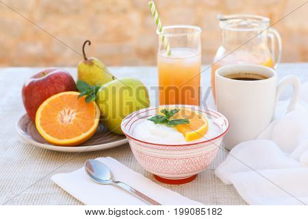 Yogurt, fruits pear, apple, orange, freshly squeezed orange juice and cup of coffee for breakfast on a light wooden table healthy breakfast concept. Horizontal. Daylight.