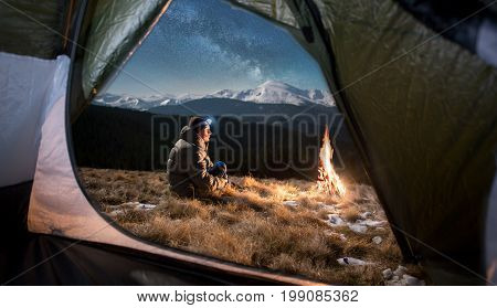 View From Inside A Tent On The Male Tourist Have A Rest In His Camping In The Mountains At Night. Ma
