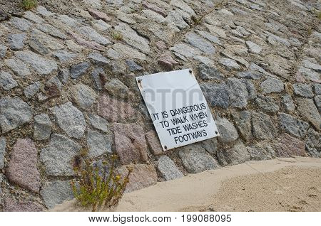 Warning sign on path being affected by coastal erosion