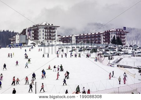 January 13 2017 picture of the hotel on a hill in a ski resort many skiers and snowboarders ride in front of the building. Ukraine Bukovel resort