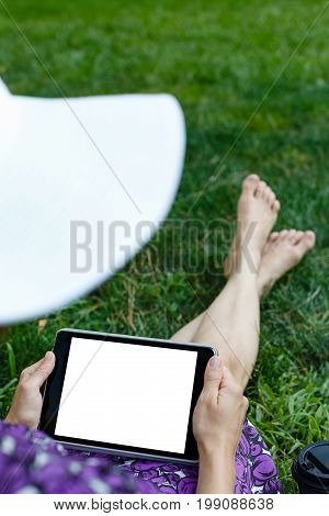Anonymous woman in white hat and dress relaxing on green grass with tablet. Rear view. Crop shot with horizontal orientation screen template.