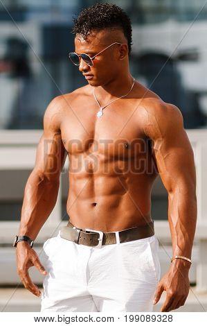 A muscular sports guy with a beautiful body. Hot Man posing among city buildings. Athletic man fitness model with a sports body. A guy in sunglas on the street among buildings and shop windows.
