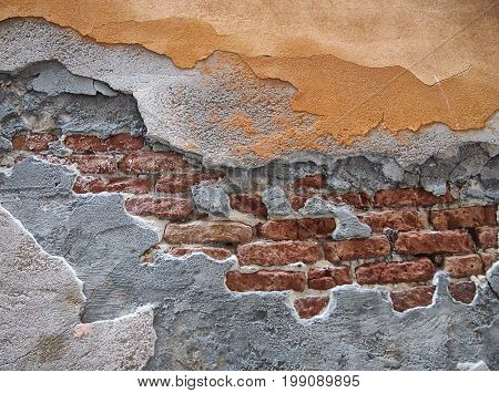 ancient damaged red brick wall with layers of cracked peeling piaster and cement and fading yellow paint
