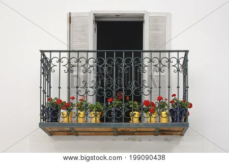 An iron balcony with red flowers in Tarifa south of Spain