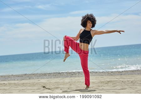 Young Afro American Sportswoman Standing On One Leg On Beach