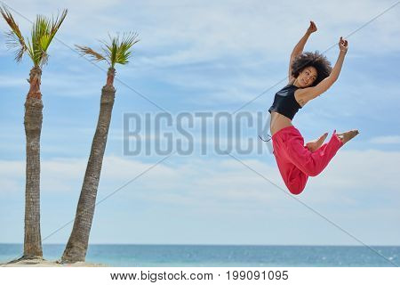 Young Pretty Sportswoman Dancing Jumping On Beach