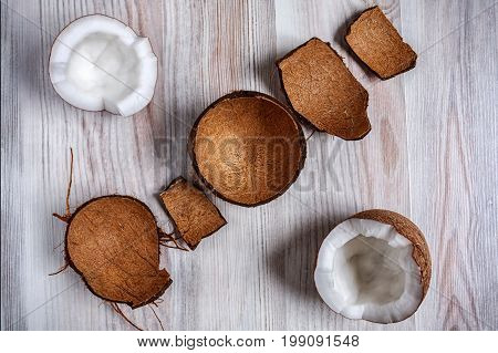 On the light surface of the table is two half the coconut in the hairy shell close up. Next to the coconut are the remains of a shaggy shell.