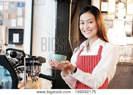 Young asian women Barista holding coffee cup with smiling face at cafe counter background small business owner food and drink industry concept