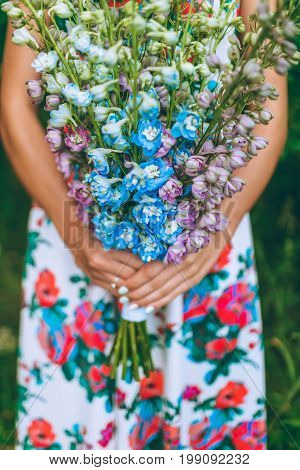 Close-up Image Of Young Woman Holding A Bunch Of Delphinium Flowers. Bridal Bouquet Idea. Floral Bac