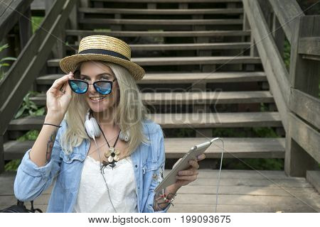 Beautiful young blonde hipster woman with glasses looking at camera in the Park with tablet in hand, sitting on the wooden steps. The woman is dressed in a denim shirt and white summer dress. Outdoor