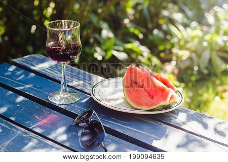 Watermelon sunglasses and glass of red wine on rustic blue table in summer garden